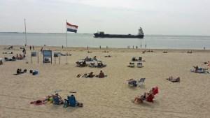 Strand von Vlissingen mit Badegästen und nahem Containerschiff