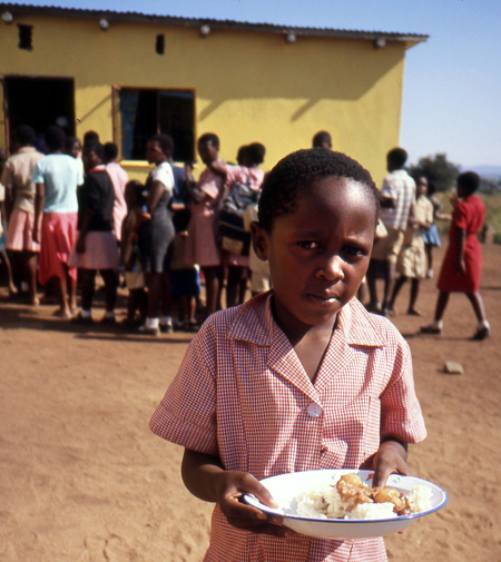 A preschool girl having received her daily ration