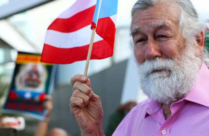 Norberto Gonzalez Claudio, who completed a prison sentence for his role in a 1983 holdup in Connecticut carried out by Puerto Rican militants, waves a miniature Puerto Rican flag as he's greeted by supporters at the international airport in Carolina, Puerto Rico, Thursday, Jan. 15, 2015. The 69-year-old Puerto Rican arrived Thursday in the U.S. territory just hours after he was released from a prison in central Florida. (AP Photo/Gerardo Bello)