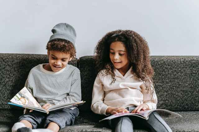 happy adorable black children speaking while reading books