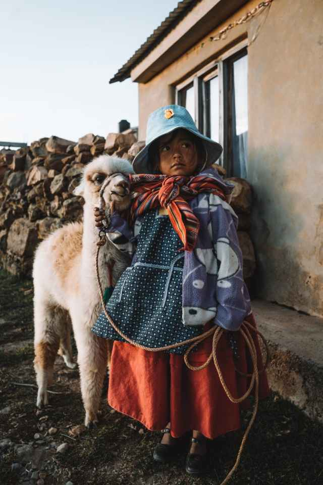 young girl holding the rope on a white alpaca close to a house Bolivia