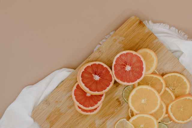 cutting board with sliced citrus fruits on napkin