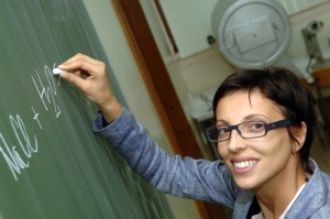 Woman writing chemistry formula on chalkboard.