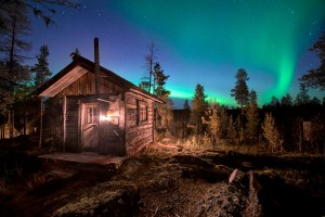 Wooden house in forest during Aurora Borealis