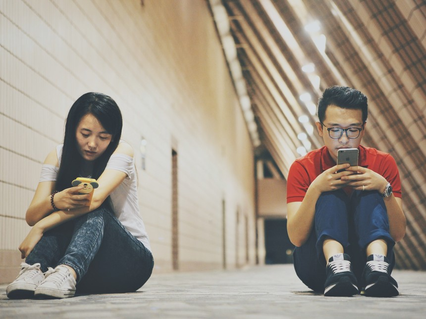 Dos-jovenes-que-se-ignoran-y-prestan-atencion-a-sus-telefonos-moviles