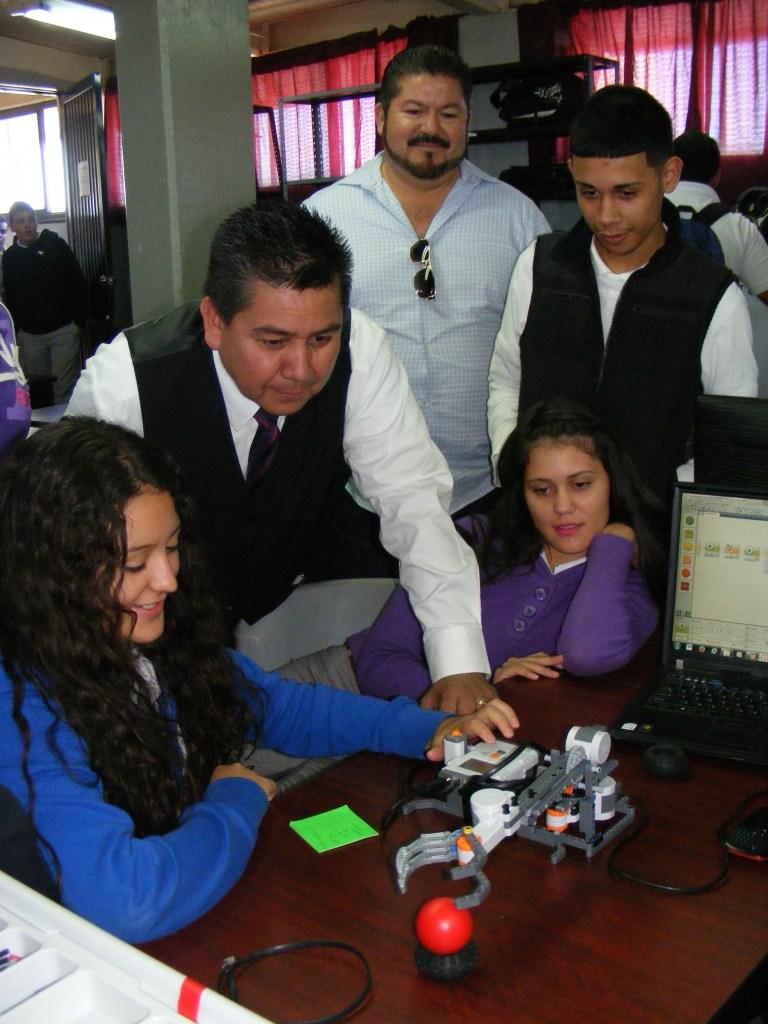El director del plantel, Cuauhtémoc Martínez, observa uno de los robots, acompañado de alumnos.
