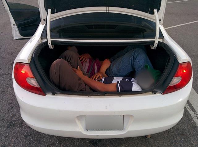 Migrantes ocultos en la cajuela de un Dodge Neon.
