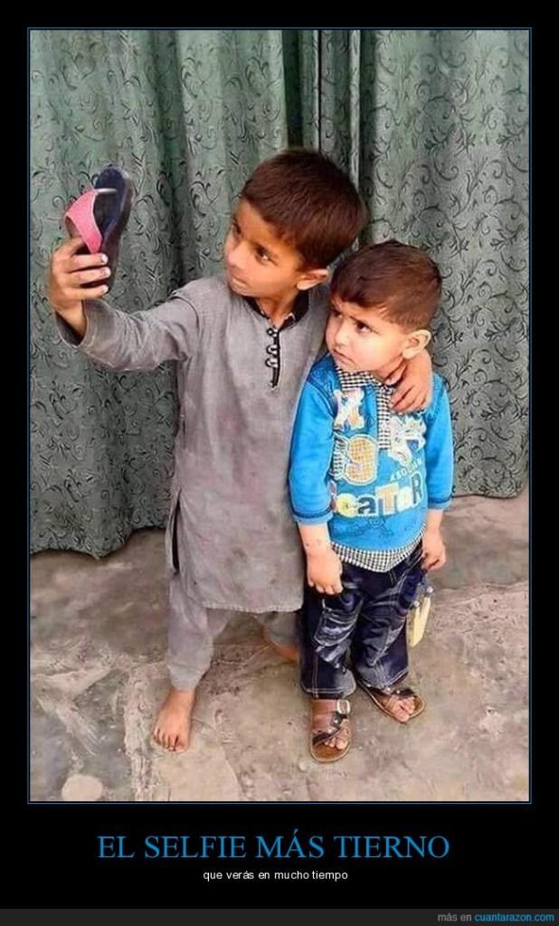 Dos niños intentando sacarse una selfie con una ojota