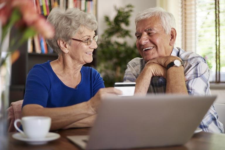 Una pareja de adultos mayores con una computadora
