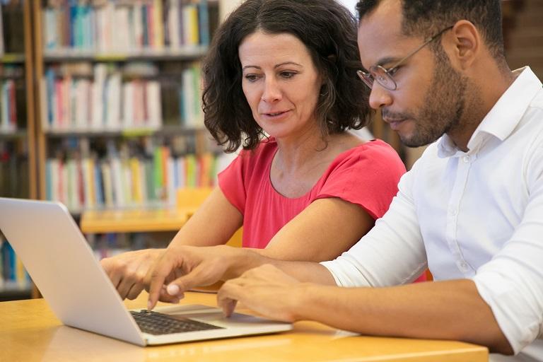 bibliotecaria y bibliotecario con una computadora