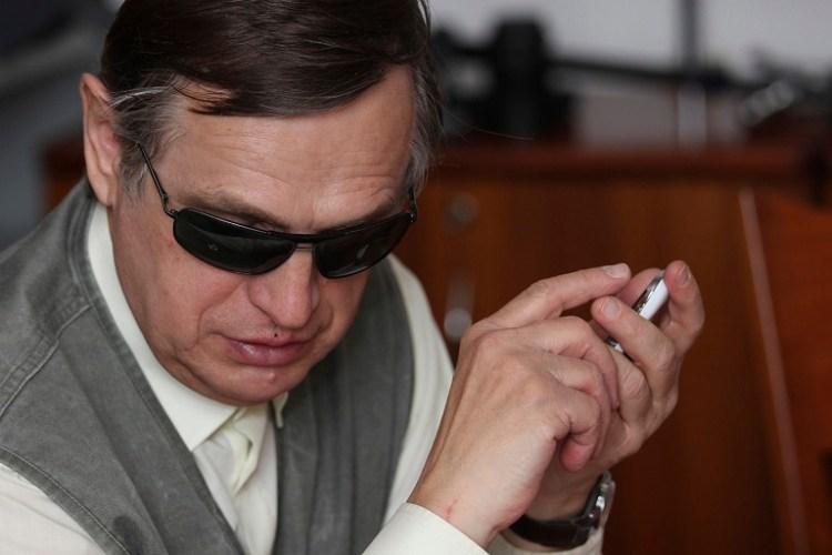 persona con ceguera escuchando un smartphone