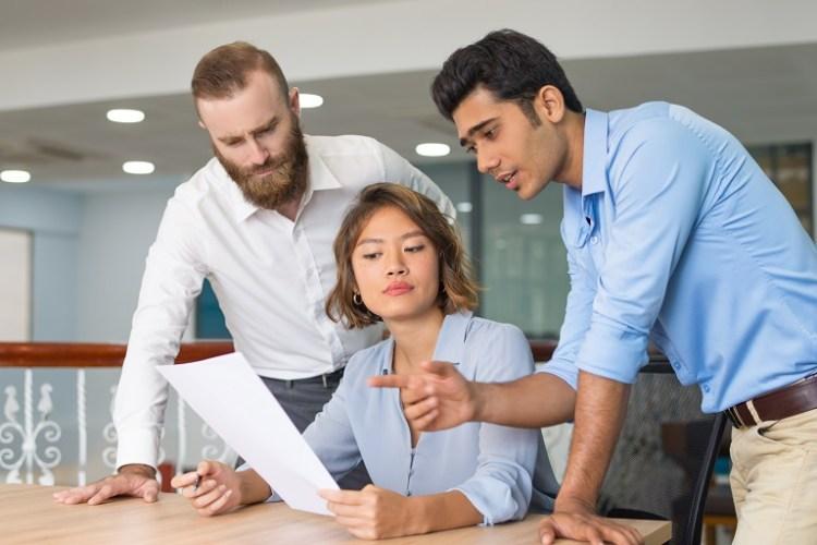 tres personas debatiendo un documento