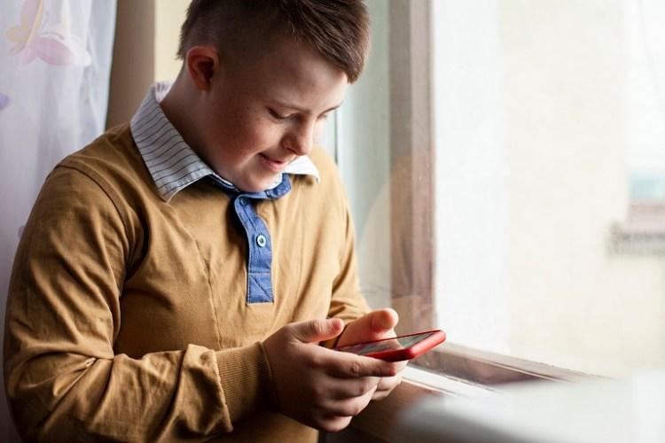 niño con síndrome de down con un celular