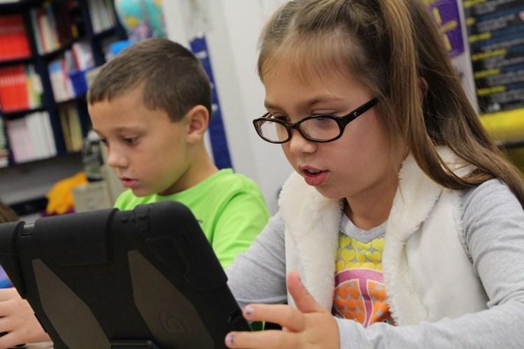 niña y niño leyendo en dos dispositvos