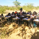 Overcrowded school teaches under tree