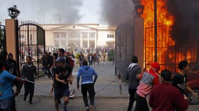 AL-AHLY CLUB SUPPORTERS RUN AWAY FROM THE FLAMES RISING FROM THE POLICE OFFICERS' CLUB IN THE EGYPTIAN CAPITAL, CAIRO