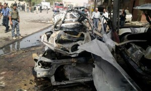 Iraqi security personnel inspect the site of a bomb attack in Baghdad
