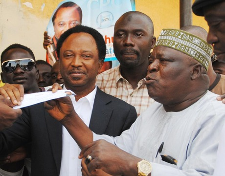 PRESIDENT, CIVIL RIGHTS CONGRESS OF NIGERIA, COMRADE SHEHU SANI (L), RECEIVING HIS APC MEMBERSHIP REGISTRATION CARD FROM THE PARTY CHAIRMAN FOR KADUNA SOUTH, ALHAJI BASHIR AHMED, DURING THE REGISTRATION EXERCISE IN KADUNA LAST MONTH