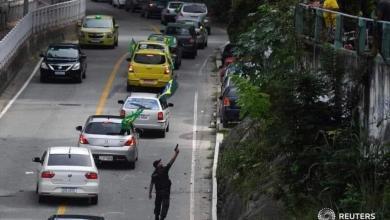 Foto de PM aponta arma para moradores que jogavam ovos em manifestantes que defendem o governo Bolsonaro