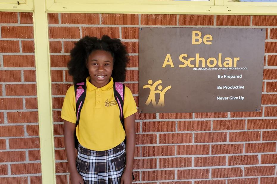 "ICCMS student standing in front of a ""Be A Scholar"" Sign"