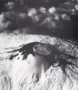 """Figura 4. Vista aerea del Cratere Centrale nel 1943, ripresa dalle forze alleate nel periodo dello sbarco in Sicilia. Il cratere è quasi interamente riempito da una colata lavica intracraterica emessa durante l'episodio parossistico di giugno 1942. In primo piano l'allora ancora molto piccolo Cratere di Nord-Est (NE). Foto pubblicata nel libro """"Mount Etna – The Anatomy of a Volcano"""" di Chester et al. (1985) (vedi bibliografia alla fine dell'articolo)."""