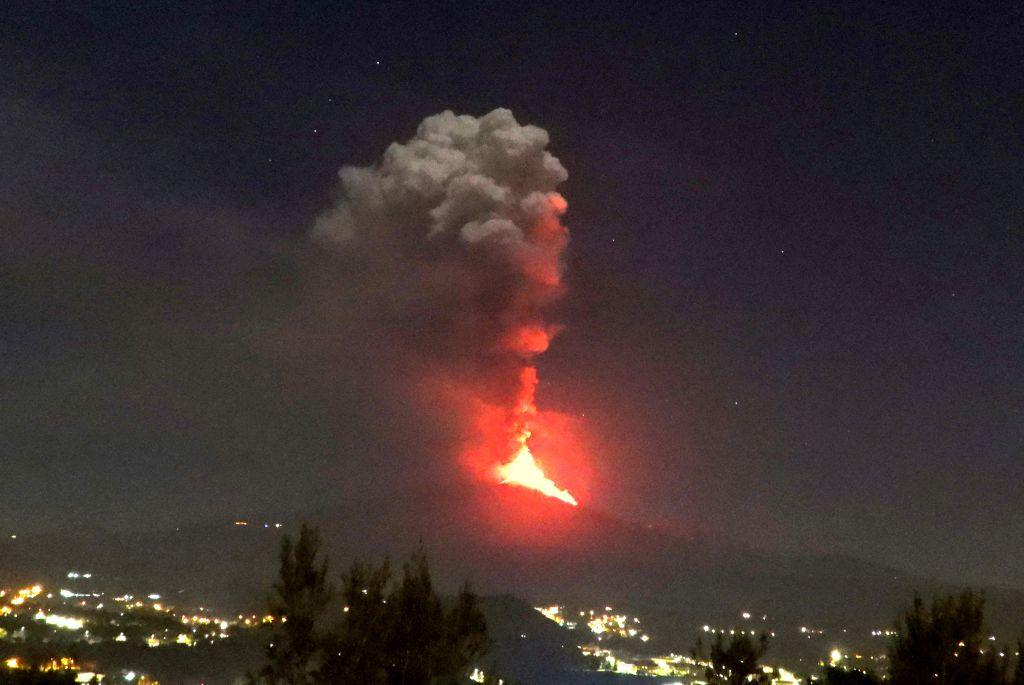 Figura 6 – Fontane di lava alte circa 300 m e colonna eruttiva iniziale che si alza circa 2 km sopra la vetta dell'Etna, verso le ore 21.00 del 24 febbraio 2021. La vista è da Trecastagni, sul versante sud-sud orientale del vulcano.