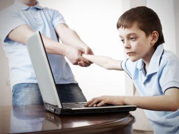 Görselde masa başında laptop ile ilgilenen bir erkek çocuğu var ve babası kolundan çekerek onu ayağa kaldırmaya çalışıyor.