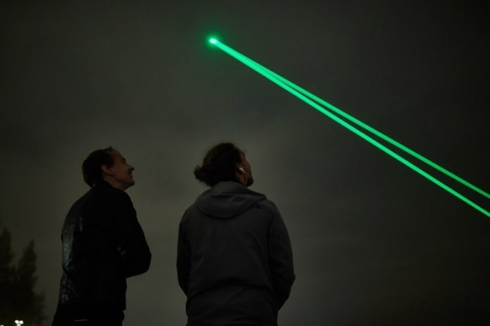 two people looking up at green laser light in the cloudy sky