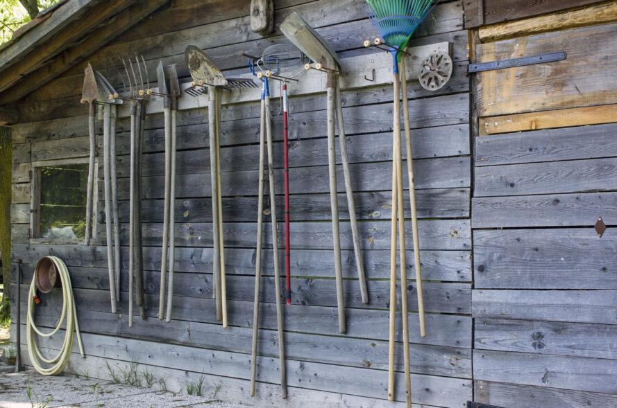 garden tools hanging on the side of a wooden shed