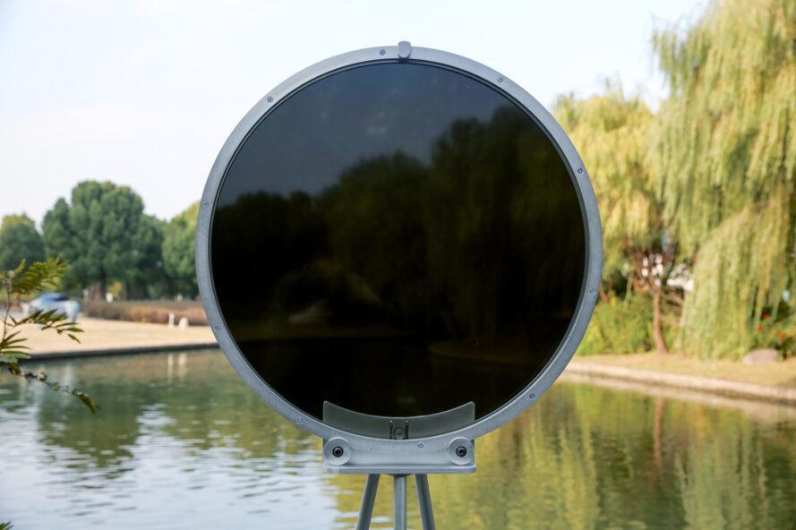 circular smog tracker device near lake with center turning dark