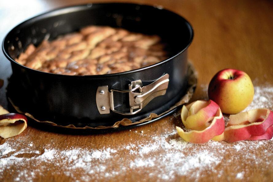 apples near apple cake in pan