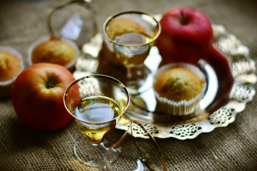 apples, apple muffins and glasses of cider on table