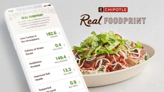 phone with emissions related to food shown on screen next to a Chipotle burrito bowl