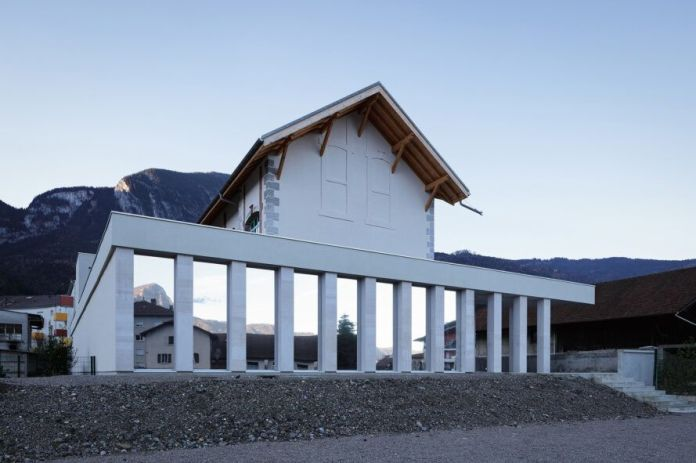 white building with gable roof and reflective facade panels