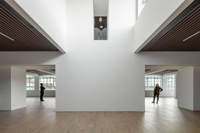 people standing inside white room with wood floors