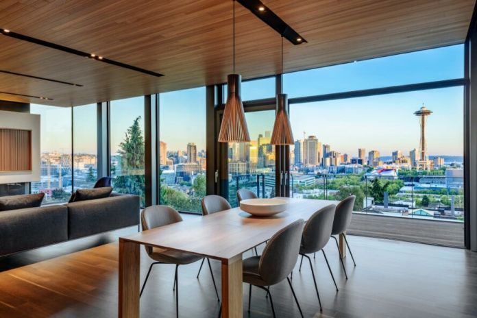 A dining area surrounded by floor-to-ceiling windows, showing a cityscape of Seattle.