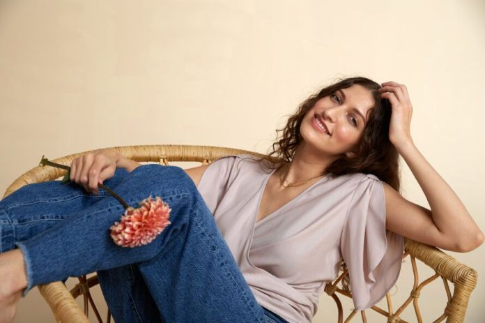 A person sitting in a wicker chair, smiling at the camera and wearing a taupe, short-sleeved shirt and jeans.