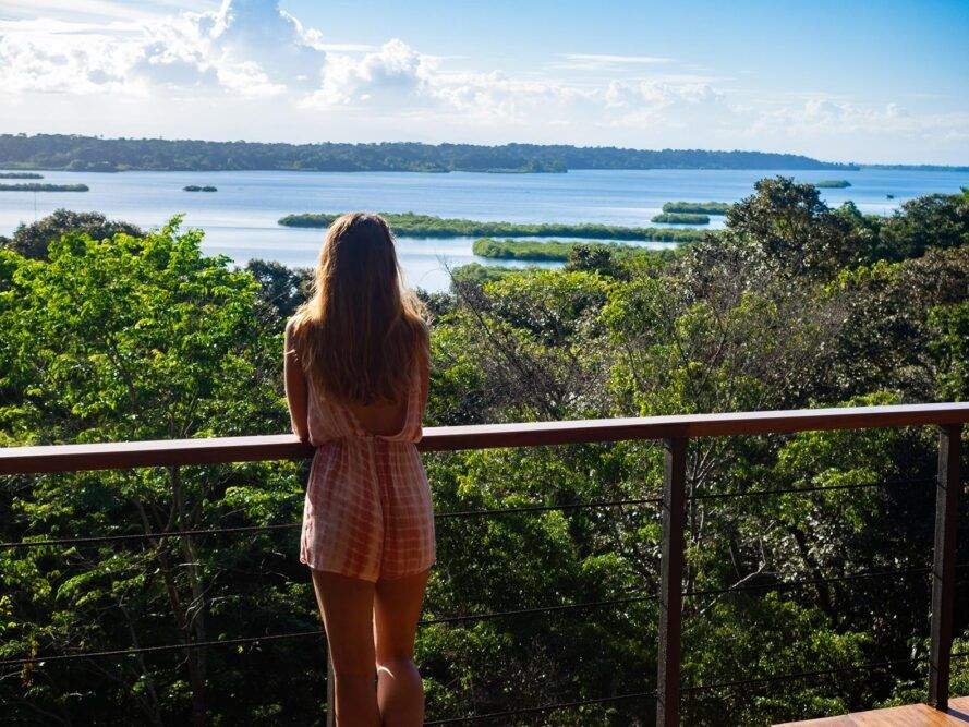 person standing on balcony looking out toward forest and water
