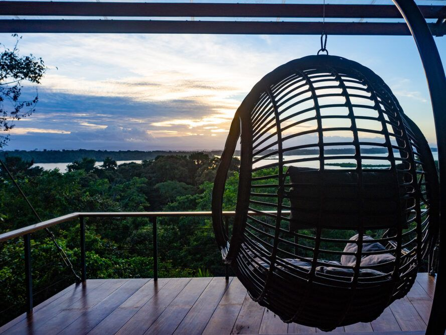 wood cocoon chair on balcony facing forest