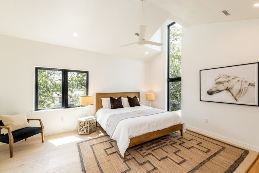 A neutral bedroom with white walls, ceiling and floors. A woven rug sits underneath a white bed, and two large windows show greenery outside.