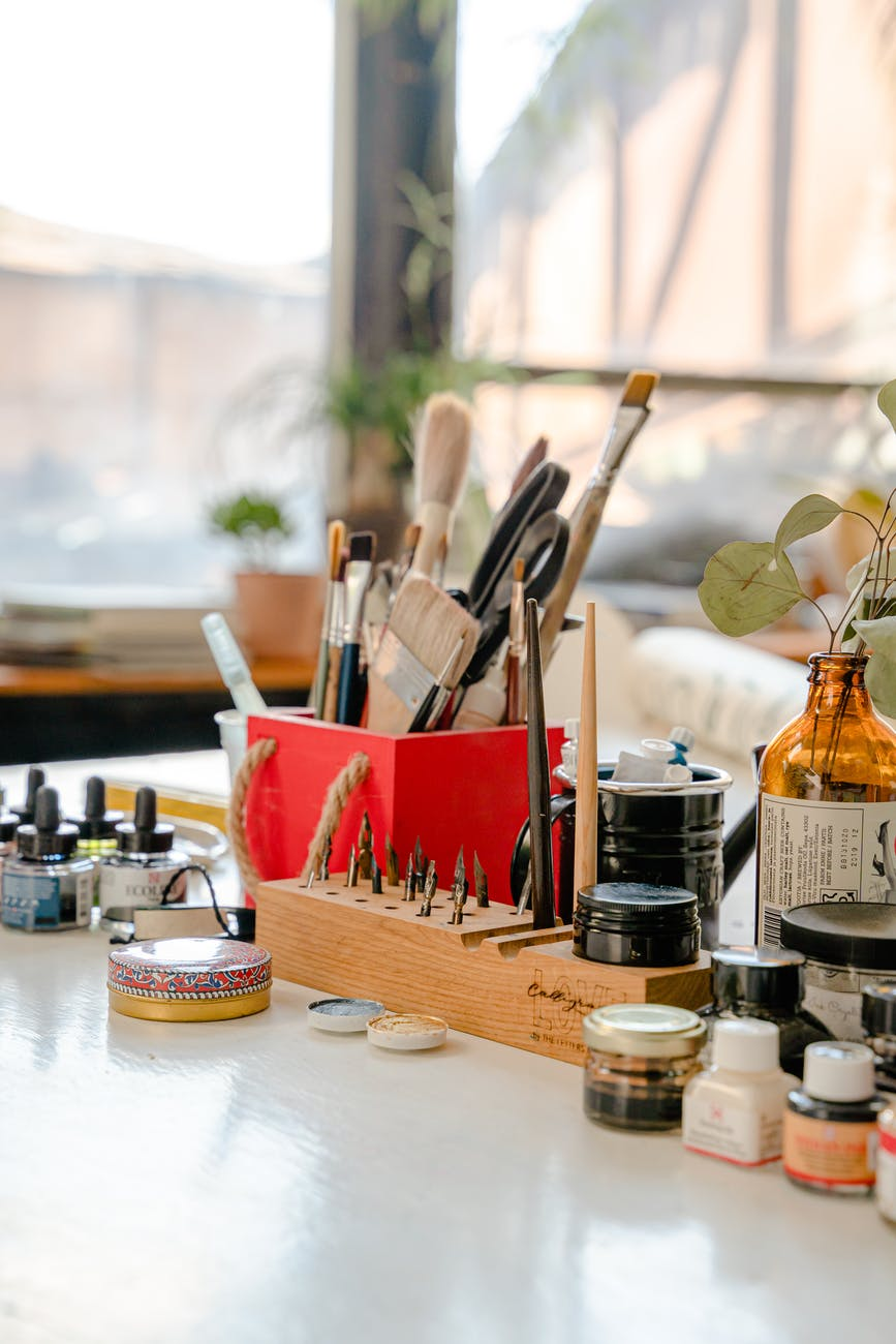 set of paint brushes and ink bottles on table