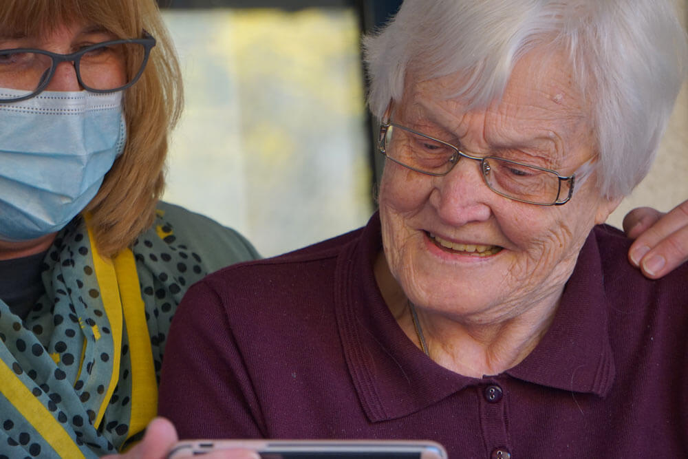 Elderly woman and daughter wearing a mask looking at a mobile device for ordering medicine online