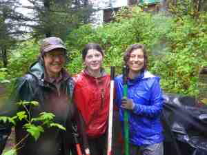 Volunteers Molly Kemp, Linnea Lentfer, and Laura Marcus pose in the rain. How many organizations have people willing to work for free behind shovels in the rain? We at Inian are thankful every day to our wonderful volunteers.