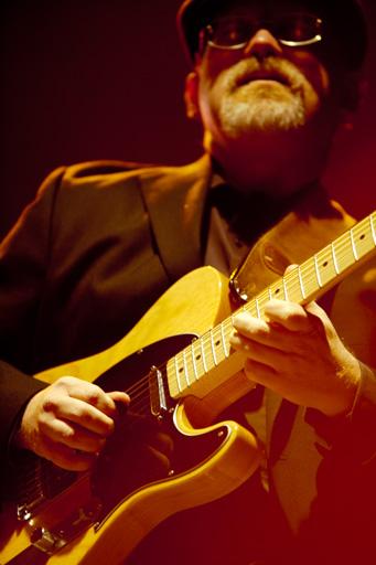 Gros plan sur les mains du musicien tout en gardant en second plan la concentration sur son visage.