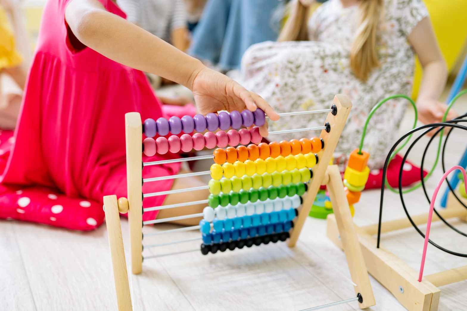girl holding multi colored wooden abacus