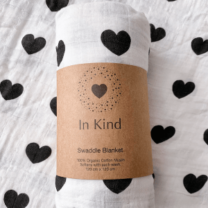 white cotton swaddle blanket with a black heart pattern