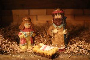 Stroh, eine Box aus Pappe, Backsteine im Hintergrund, nur der Vordergrund ist gut zu sehen. Geschnitzte und bemalte Holzfiguren: Links kniede Frau mit gefaltenen Händen, lächelnd; rechts Mann mit Bart und Holzstab; vorbe Krippe mit Stroh und schlafenden Baby, zugedeckt.