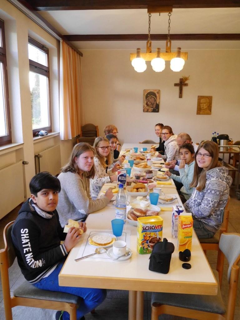In einem schlichten Raum sitzen Kinder an einer Tischreihe und frühstücken. Der Tisch ist reich gedeckt. Sie halten ihre Brötchen oder warten, bis der Fotograf fertig ist. Alle blicken zur Kamera.