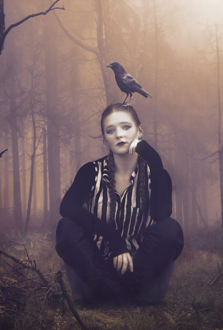 A girl sits with crossed legs with a crow on her head.