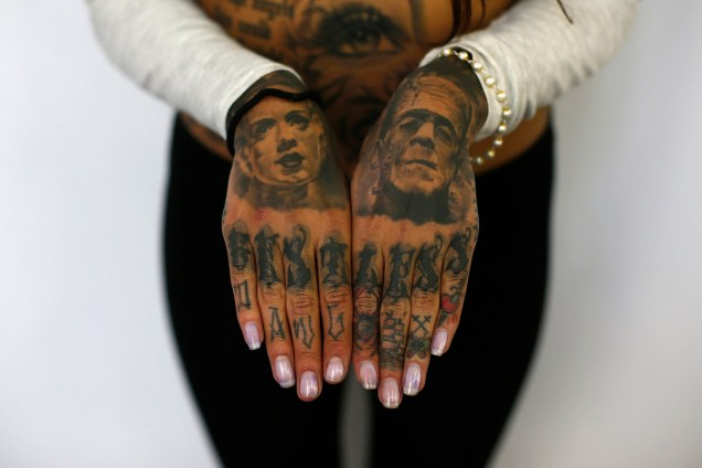 Cleo displays tattoos on her hands during the ninth London Tattoo Convention in London